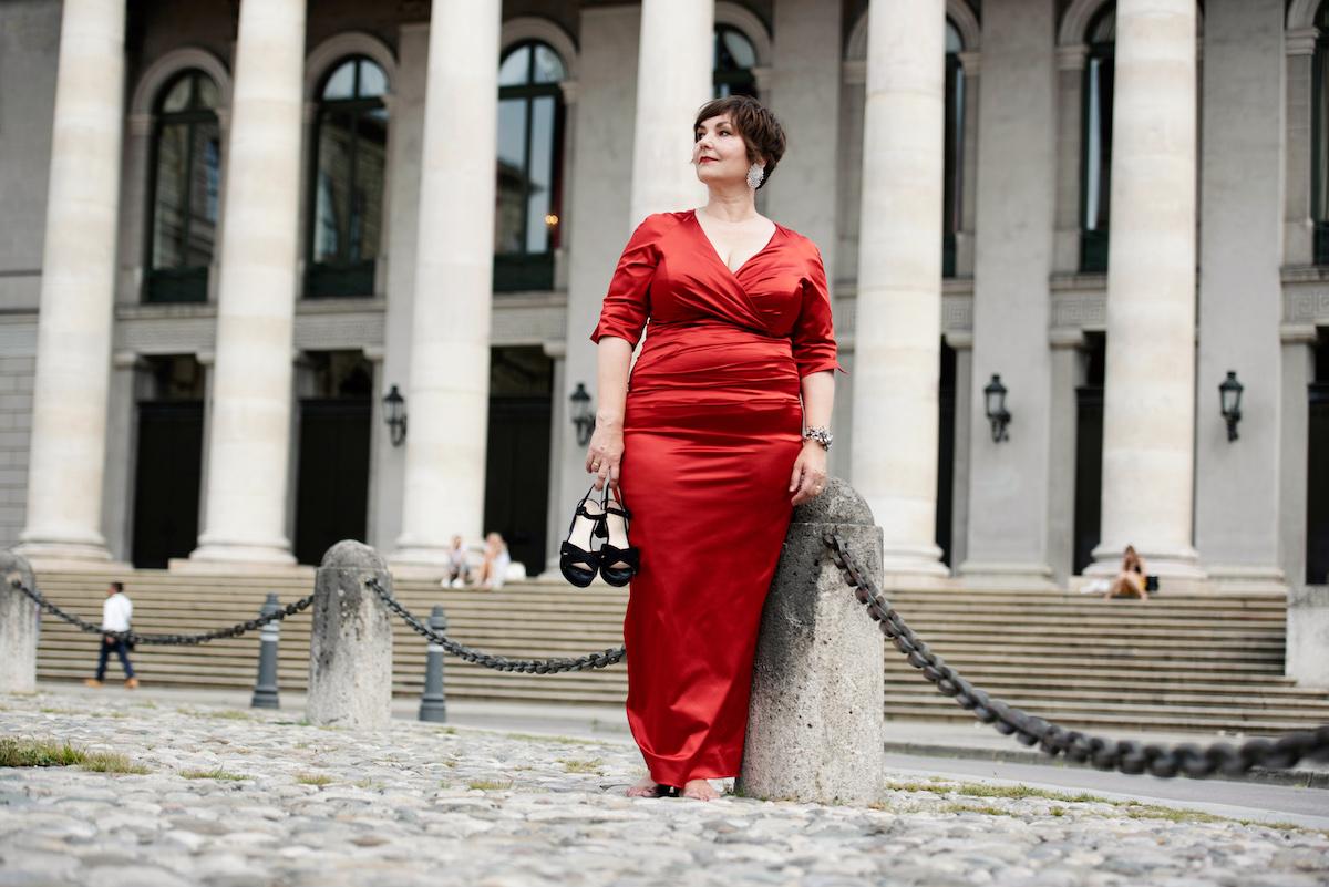 Susanne Ackstaller im roten Kleid vor dem Nationaltheater in München.