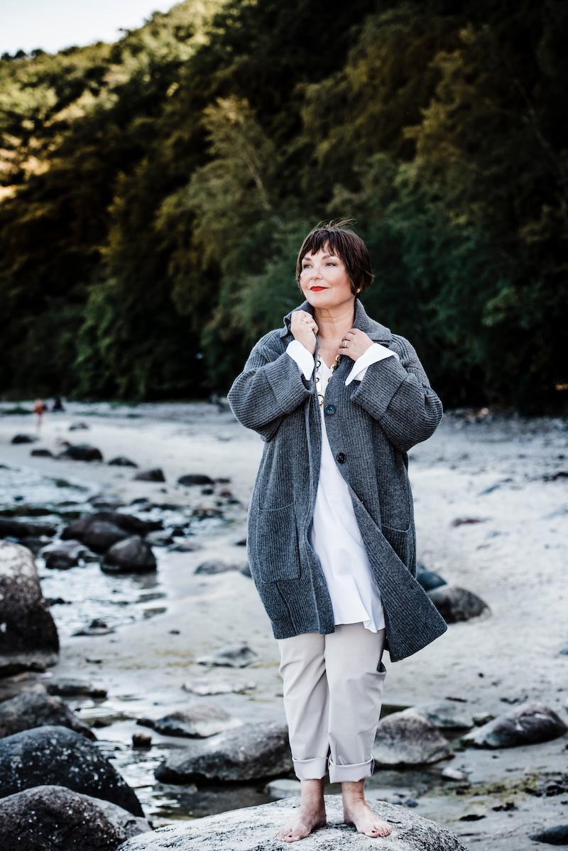 Susanne Ackstaller aka Texterella in einer Strickjacke von Sallie Sahne am Meer auf Rügen.