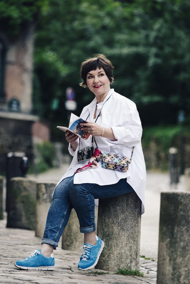 Texterella Susanne Ackstaller liest einen Parisreiseführer. An den Füße: Sneakers in türkis von UXGO