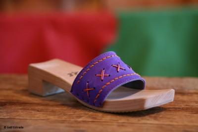 Schlichte Clogs aus mittelbraunem Holz. Das Lederband ist breit, lila und mit einem grafischen Muster in rot bestickt.