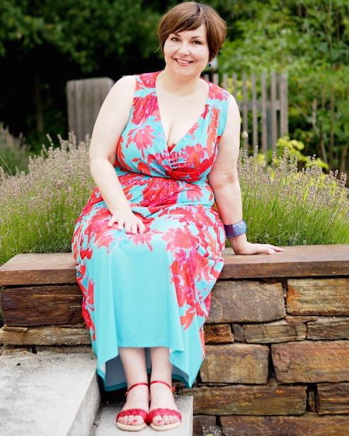 Türkises Kleid mit korallroten Blüten in Sizeplus: Susi Ackstaller aka Texterella auf einer Mauer sitzend