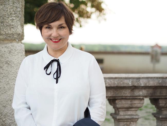 Typisch Pariser Stil: Schmale gemusterte 7/8-Hose, schlichte Bluse mit Schleifchen, Trenchcoat, Ballerinas, rote Lippen