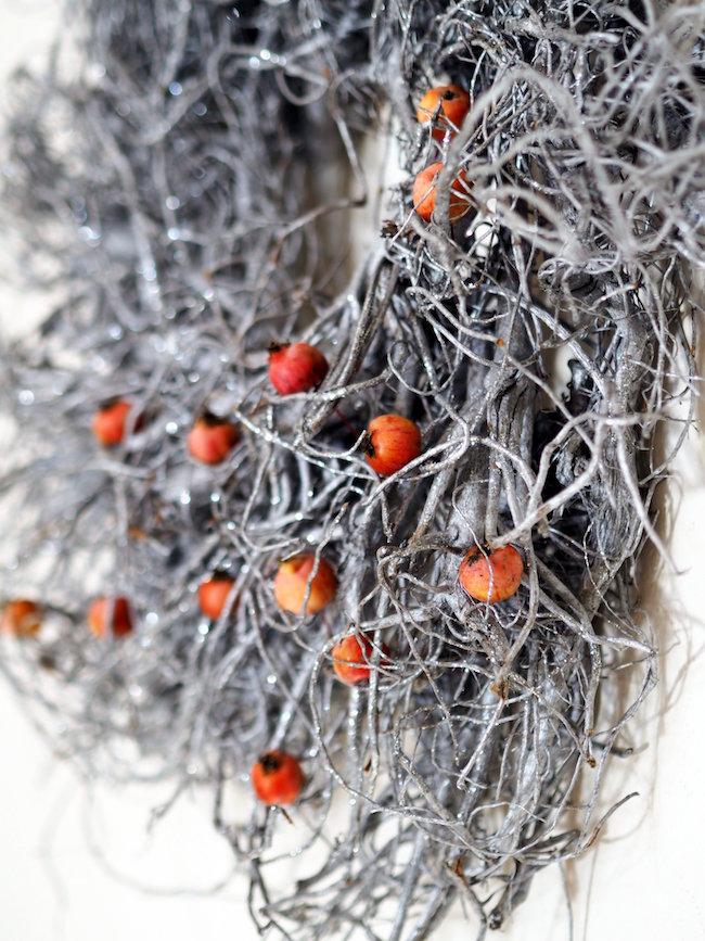 Weihnachtsdeko: Silberner Kranz mit eingesteckten Zieräpfeln