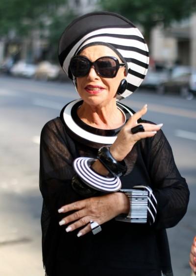 Alte Dame, ganz in Schwarz-Weiß, mit auffälligen Streifenhut und XXL-Sonnenbrille