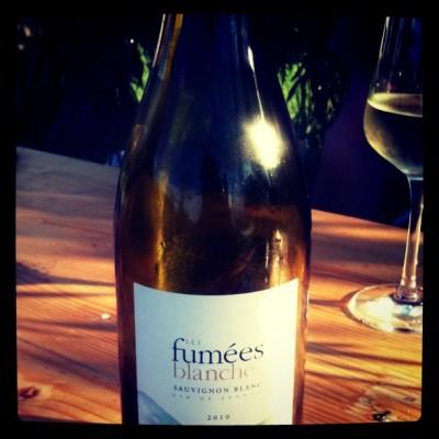 Eine Flasche Sauvignon Blanc auf einem Holztisch, im Hintergrund ein Weinglas.