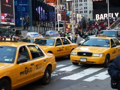 Downtown New York. Eine Straßenszene mit drei der berühmten gelben Cabs im Vordergrund.