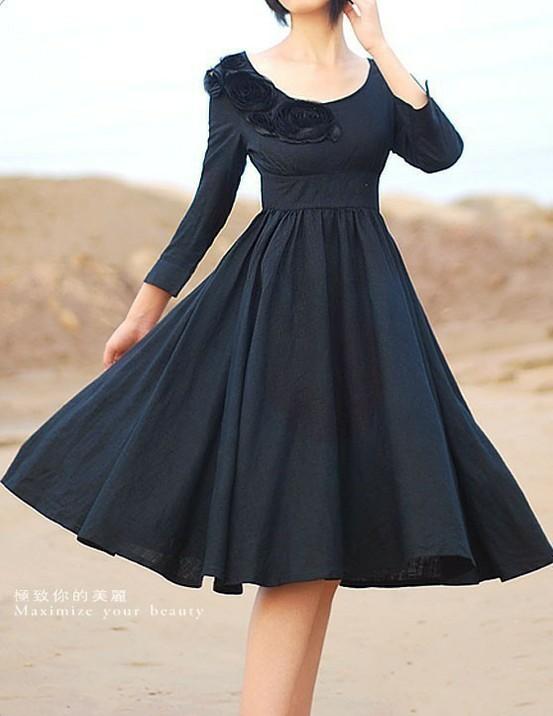 Schwarzes, weitschwingendes Kleid mit etwas höherer Taille. Der Ausschnitt ist rund und mit Blumen plastisch verziert.