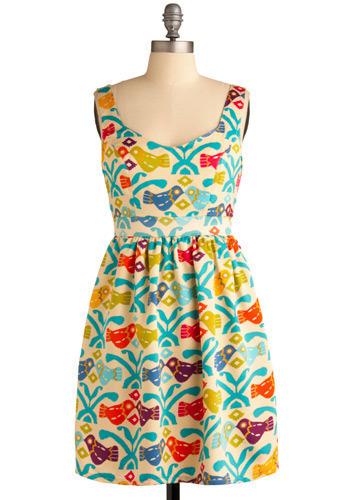 Ein cremefarbenes tailliertes Kleid, bedruckt mit bunten grafischen Vögeln.